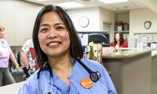 Nurse standing at counter with button on scrubs